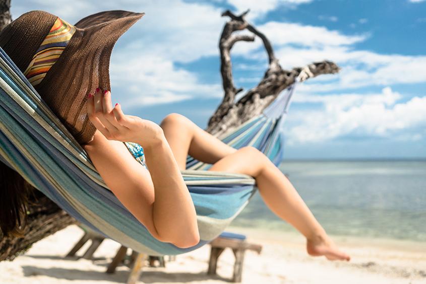 Frau am Strand entspannt in Hängengematte am Meer sonnenschutz-sonnenbrand-kosmetik-studio-stuttgart-carola-kiesel-beauty-balance